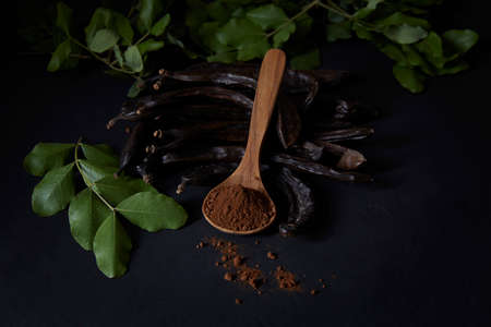 In the foreground, a wooden spoon with carob flour. Around and at the bottom, pods and carob leaves. All on black background. Montuiri, Mallorca, Spain