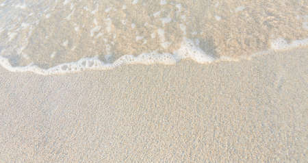 Close-up of white sand, washed by soft sea waves