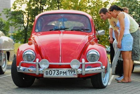 MOSCOW,RUSSIA-JULY 31: Two unidentified person look in red vintage Volkswagen Beetle  on exhibition parking show of retro-cars Night Moscow Classic Rally-2010 on July 31,2010 in Moscow, Russia