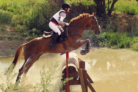 MOSCOW - AUGUST 21: Rozanov Menshikova Julija on Veleria a Russian Cross-Country Championship, August 21, 2010 in Moscow, RussiaRider horseback on jumping brown chestnut horse inwaters splashes Editorial