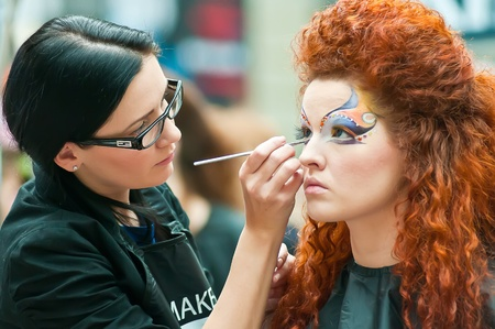 MOSCOW, RUSSIA - FEBRUARY 12: Stylist and his model prepare for the VIII Open Championship for creative makeup KOSMETIK international on February 12, 2011 in Moscow, Russia.