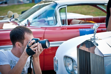 MOSCOW - JULY 31: Photographer and retro car on exhibition parking at an annual event the VI race of vintage cars Night Moscow Classic Rally. July 31, 2010 in Moscow, Russia