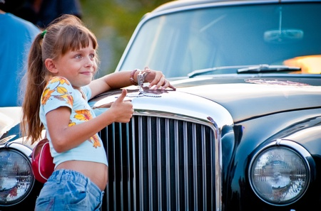 superleggera: MOSCOW, RUSSIA-JULY 31: Little Girl and retro car  in exhibition parking at an annual event, the VI race of vintage cars Night Moscow Classic Rally. July 31, 2010 in Moscow, Russia Editorial