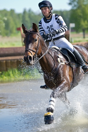 MOSCOW - JUNE 02  Unidentified rider on horse  Equestrian sport  Rider eventer on horse negotiating cross country fence Water jump at the International Eventing Competition CCI3 2  1 Russian Cup Eventing June 02, 2012 in Moscow, Russia