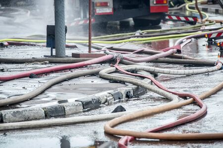 extinguishing: fire hoses on the sidewalk of asvalte in water flows after extinguishing