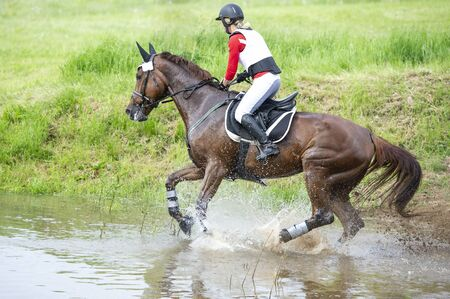 Eventing: equestrian rider jumping over an obstacle.