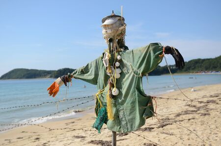 Scarecrow made of plastic and other rubbish thrown out of the sea. Plastic, nets, barbed wire, sinks. By the sea on the beach 免版税图像