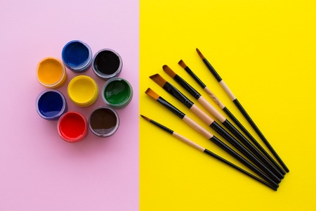 Beautifully arranged cans of primary colors on a pink background, as well as a set of brushes for drawing on a yellow background.