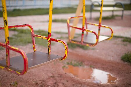 Bright, new beautiful swing on the Playground in the yard and a puddle.