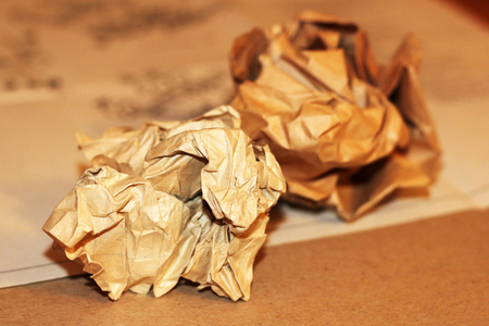 Close-up of crumpled paper balls on a white wooden background with pencils and pencil shavings. Creative.