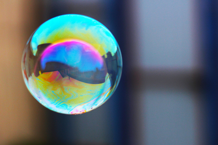 Soap bubble with the reflection of buildings inside. Colored.
