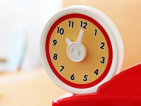O'clock round toy clock, plastic object, red color Фото со стока