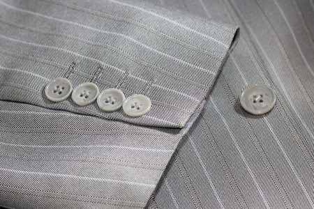 Closeup of suit buttons for business or formal wear, grey color