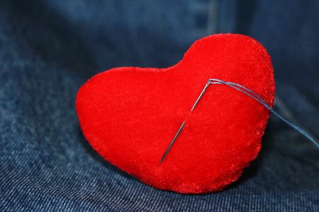 Heart shaped pincushion on jeans background, object