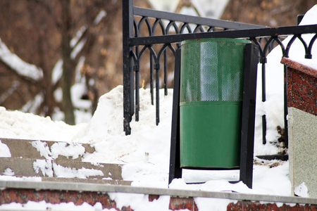 Green recycling bin container or garbage Trashcan on the street of city, winter Stock Photo