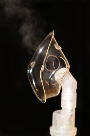 Compressor nebulizer at work, isolated on black background, object Stock Photo