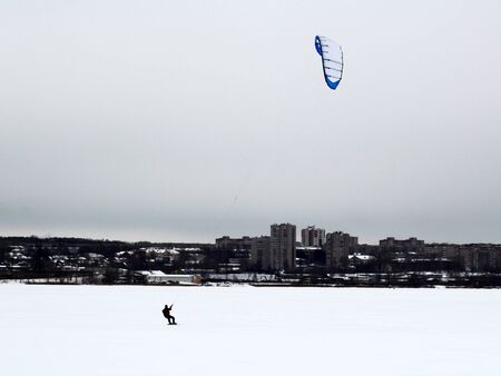Male athlete Snowboarder on snowboard jumps with kite on free ride. kiting. Winter.