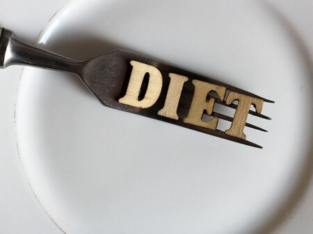 Empty white plate and fork, diet inscription in wooden letters, health