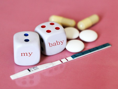 Pregnancy test positive with two stripes and contraceptive pill. The dice on pink background. Health. Foto de archivo