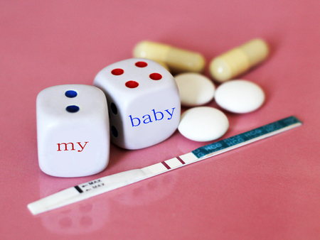 Pregnancy test positive with two stripes and contraceptive pill. The dice on pink background. Health. Stock Photo