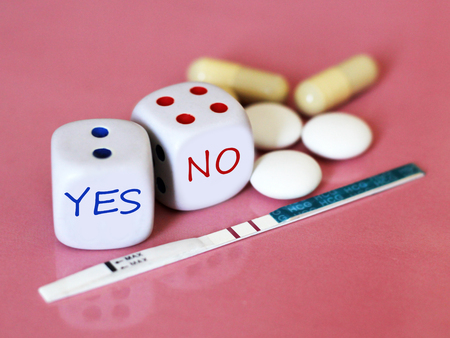 Pregnancy test positive with two stripes and contraceptive pill. The dice on pink background. Health. 스톡 콘텐츠