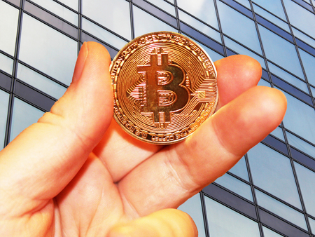 bitcoin in hand on building background, cryptocurrency