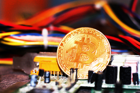 Golden Bitcoin virtual currency on a circuit board background, object