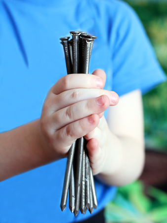 Childrens hands hold iron nails, close up Stock Photo
