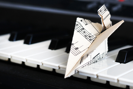 13 March 2018 Russia, Izhevsk. Close-up music score on piano keyboard, airplane of paper, object Stock Photo