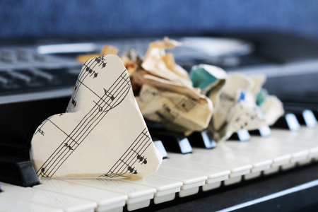 13 March 2018 Russia, Izhevsk. Close-up music score on piano keyboard, heart of paper, object