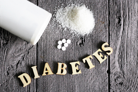 Süßstofftablette und Zucker. Hölzerne Buchstaben des Textdiabetes. Essen.