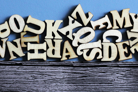 Wooden English letters in bulk and on wooden blue background, education Stock Photo