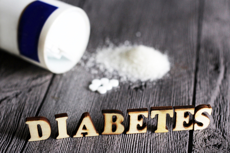 Sweetener tablet and sugar. Text diabetes wooden letters. Education