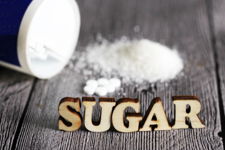 Sweetener tablet and sugar. Text sugar wooden letters. Food.