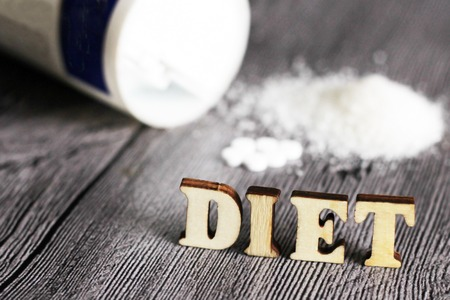 Sweetener tablet and sugar. Text diet wooden letters.