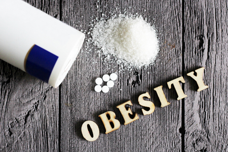 weetener tablet and sugar. Text obesity wooden letters. Food.
