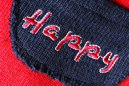 The inscription is embroidered with threads. The word happy. Red color.