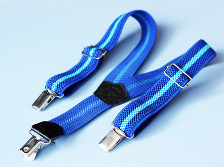 Blue suspenders clothing for baby on blue background, object Stock Photo