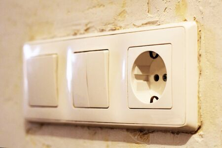 Electric light switch and socket on the empty wall, electrical power socket and plug switched, object