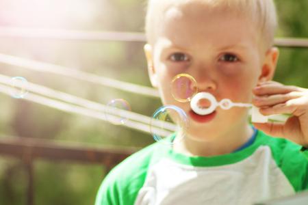 Portrait of cute little boy making soap bubbles. Summer. Archivio Fotografico