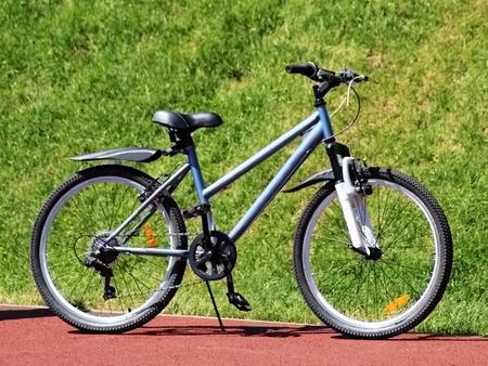 New blue women's bike on a grass background, sport