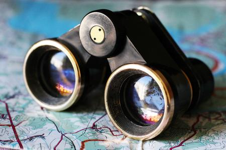 Old small binoculars on the map, retro