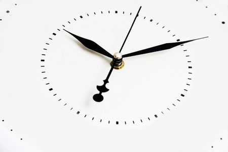 White wall clock with black arrows, close-up of the dial