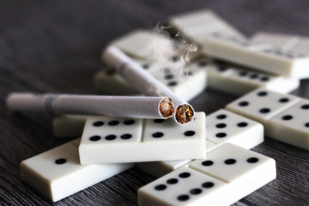 Cigarettes with dominoes so close, dangers of smoking Stock Photo