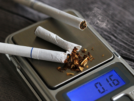 Broken cigarettes on electronic scales, dangers of smoking