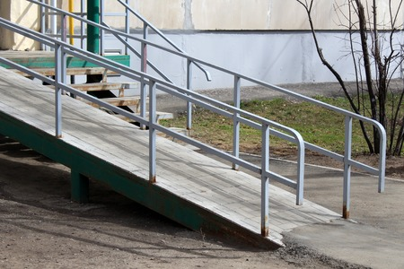 A wheelchair ramp, an inclined plane installed in addition to or instead of stairs, outdoor. Stok Fotoğraf