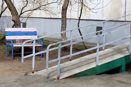 A wheelchair ramp, an inclined plane installed in addition to or instead of stairs, outdoor. Imagens