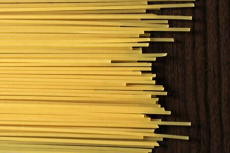 Yellow long spaghetti on wooden background, food Stock Photo