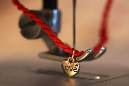 Red string with a heart of gold and a sewing machine so close