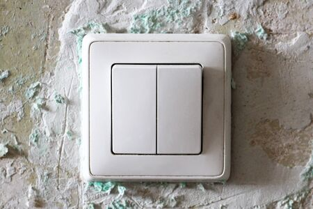 The white switch on the old plastered wall